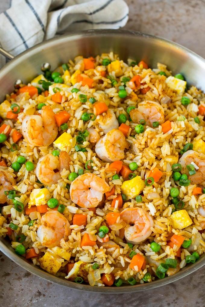 Una cacerola de arroz con camarones fritos con huevo y verduras.