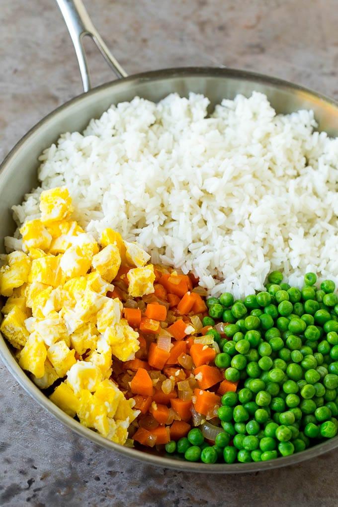 Arroz cocido, huevos revueltos, zanahorias y guisantes en una sartén.