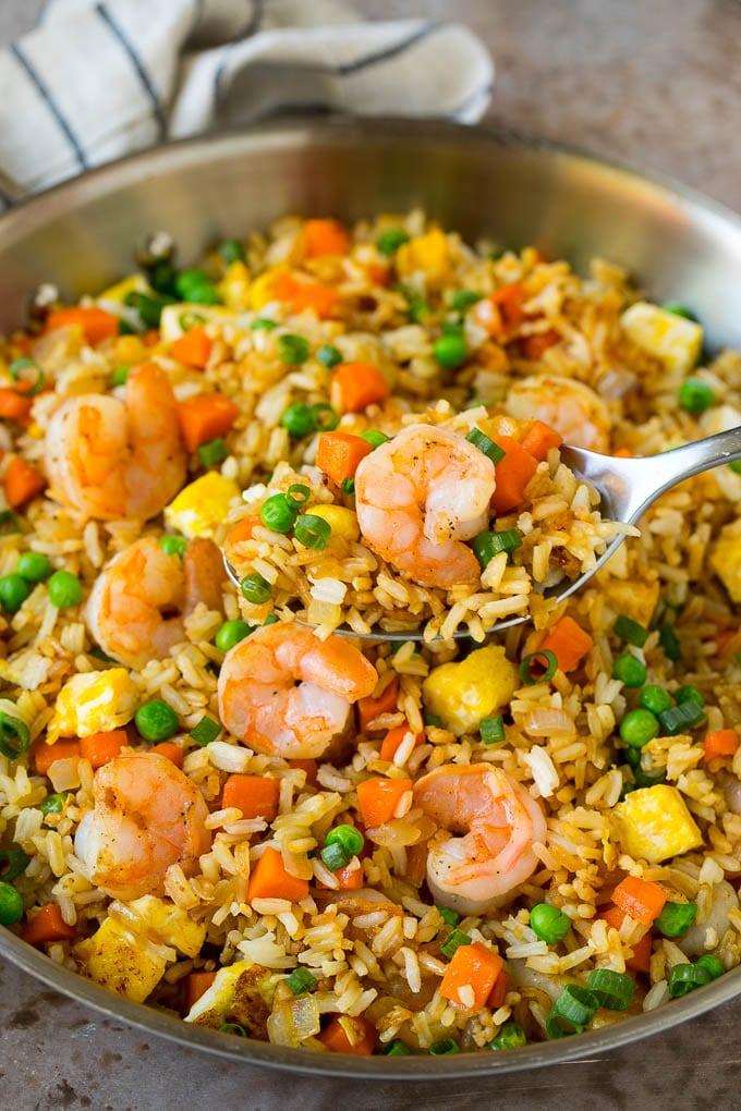 Una cuchara para servir en una sartén de arroz frito con camarones.