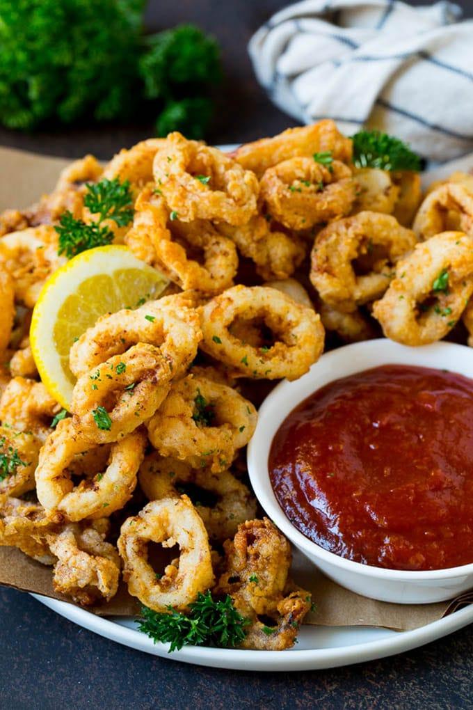 Calamares fritos con rodajas de limón y salsa cocktail.