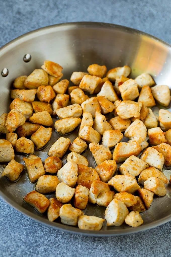 Trozos de pollo cocidos en una sartén de metal.