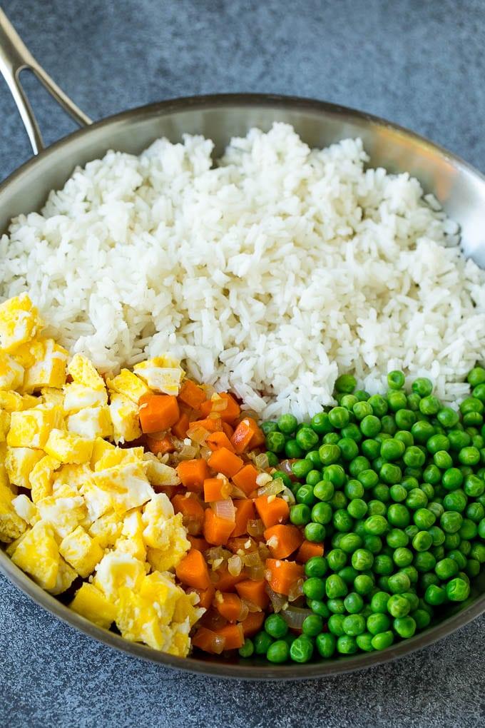 Una olla de arroz cocido, zanahorias, huevos y guisantes.
