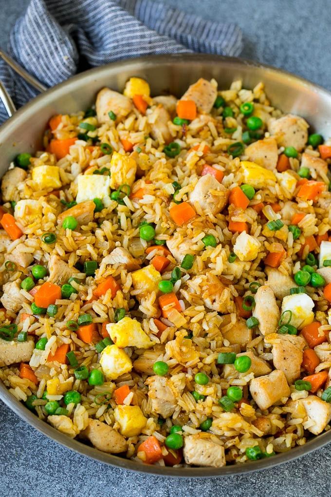 Una cazuela de arroz con pollo frito con huevo y verduras.
