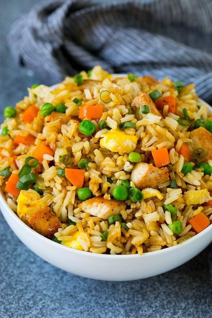 Un tazón de arroz frito con pollo cubierto con cebollas verdes en rodajas.