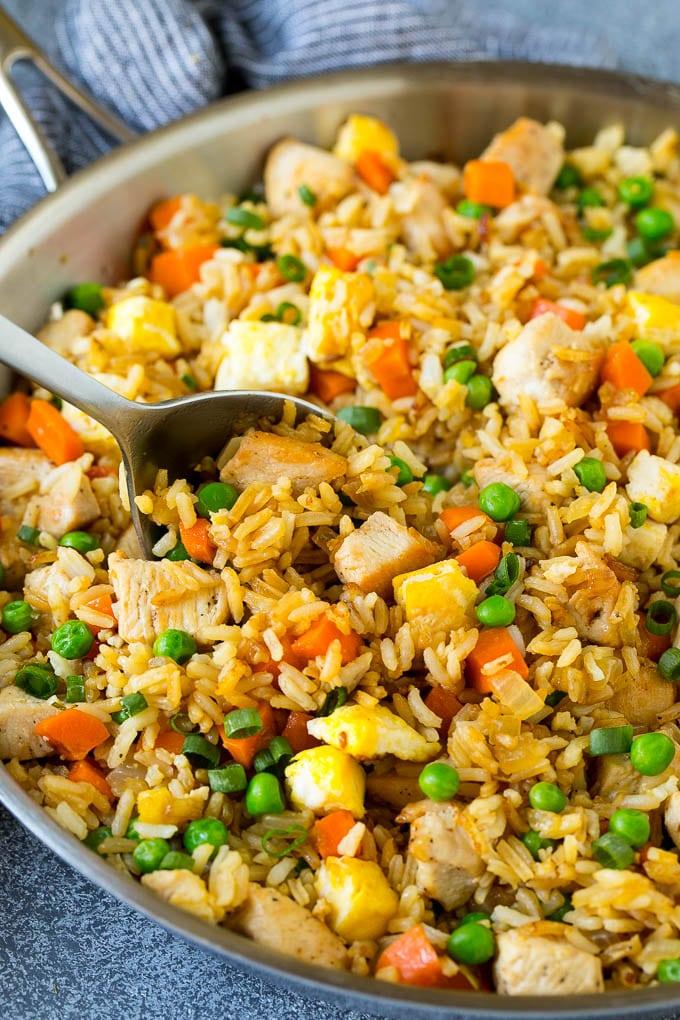 Una cuchara para servir en una sartén de arroz frito con pollo.