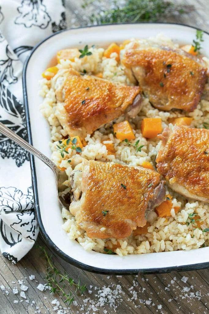 Esta sartén de pollo y arroz al horno combina pollo con arroz parmesano cremoso y calabaza para una comida completa y saludable con menos platos para limpiar.