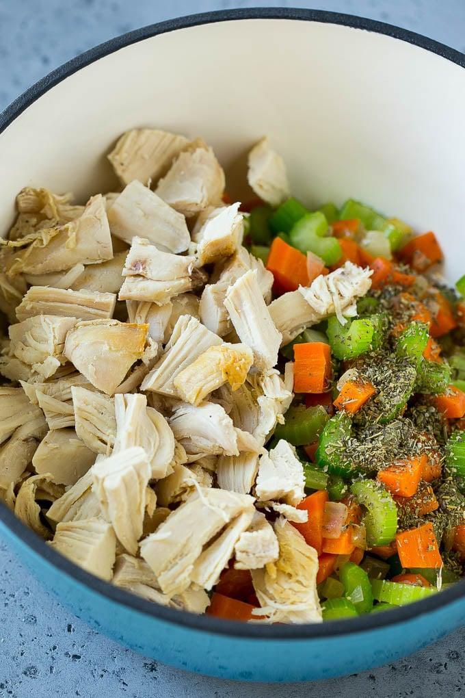 Verduras, pollo rallado y hierbas secas en una tetera.