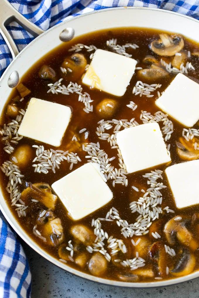 Arroz con caldo de res, sopa de cebolla y mantequilla en una sartén.