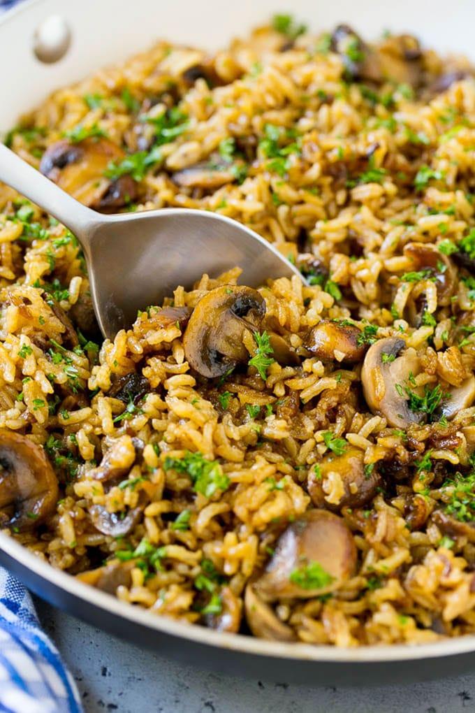 Una cacerola de arroz con champiñones fácil con una cuchara para servir adentro.