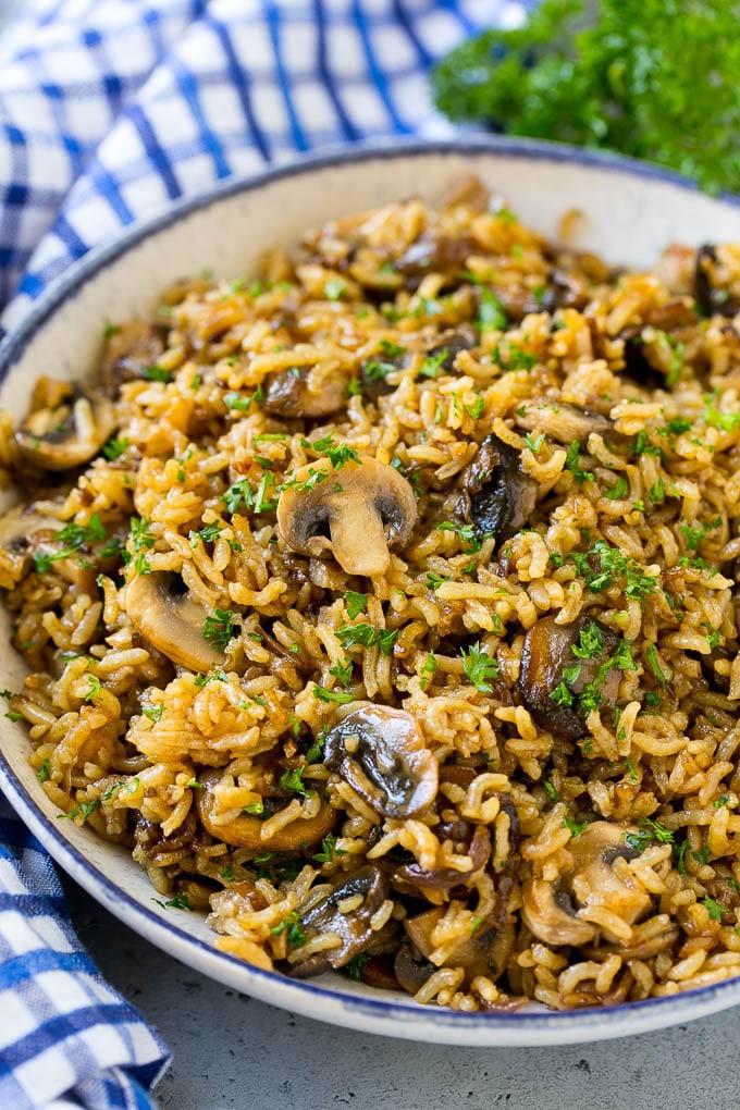 Un tazón de arroz con champiñones al horno aderezado con perejil picado.