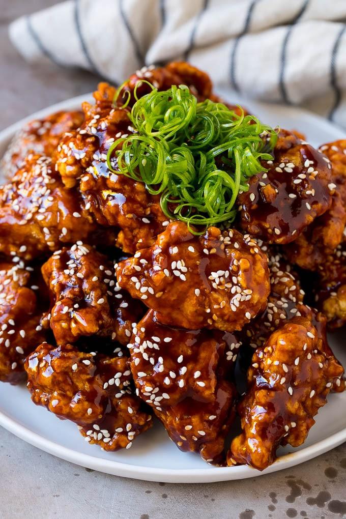 Pollo frito coreano en un plato adornado con cebollas verdes rizadas.