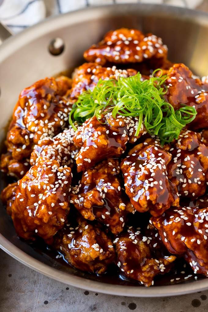 Una sartén de pollo frito coreano cubierto con una salsa dulce y picante y adornado con semillas de sésamo.