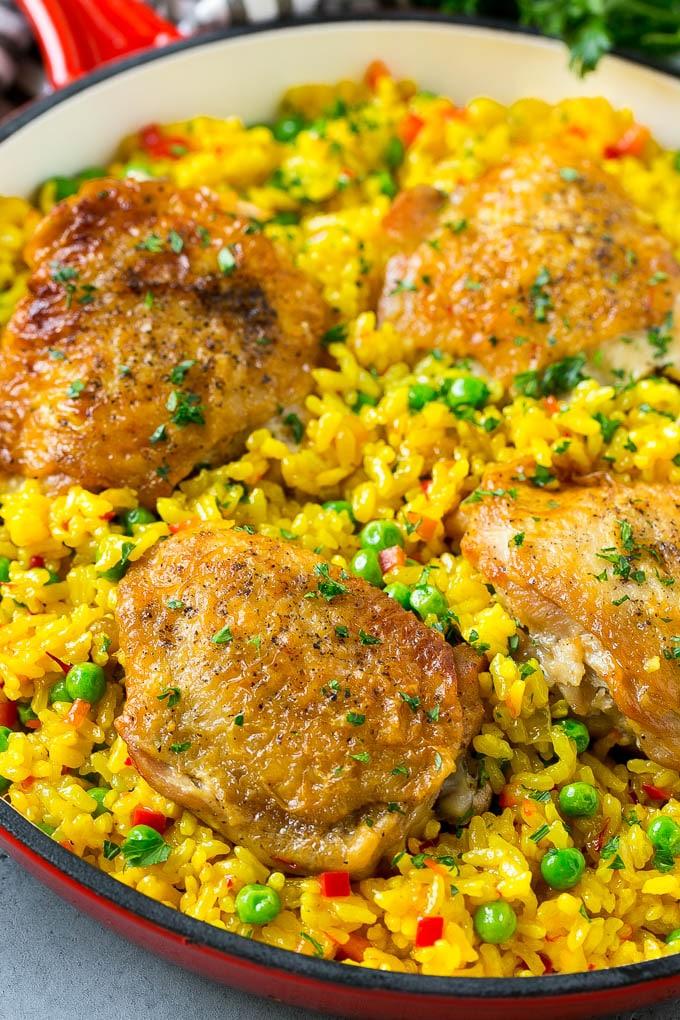 Una cazuela de arroz con pollo con muslos de pollo, arroz con azafrán y guisantes.