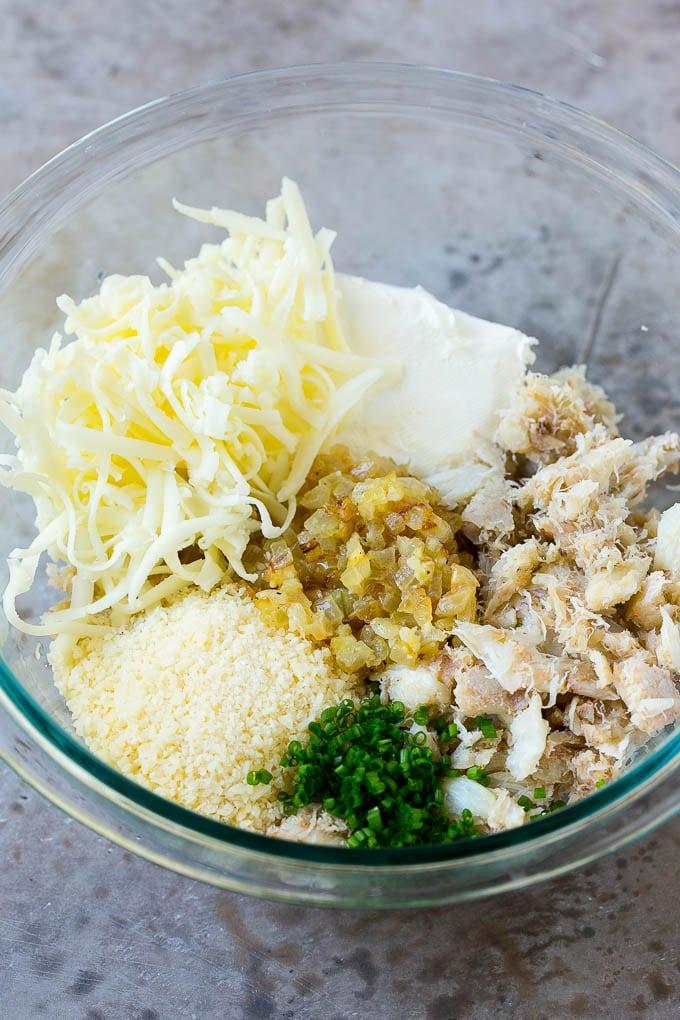 Un plato de carne de cangrejo, queso, cebollino, cebolla y ajo.