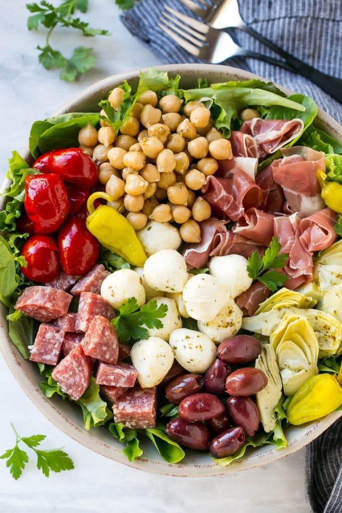 Entrante de ensalada a base de salami, pimientos, jamón, garbanzos y mozzarella.