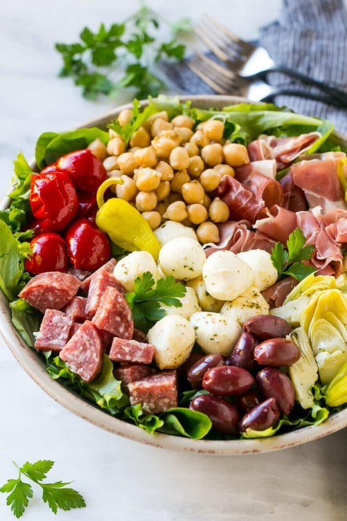 Ensalada de aperitivo con salami, mozzarella fresca y pimientos asados sobre ensalada verde.
