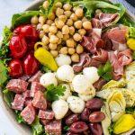 Esta receta de ensalada de antipasti está rellena de embutidos italianos, quesos y verduras, todo aderezado con un aderezo casero picante.