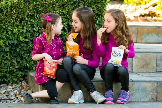 Los niños comen bolsas de papas fritas.