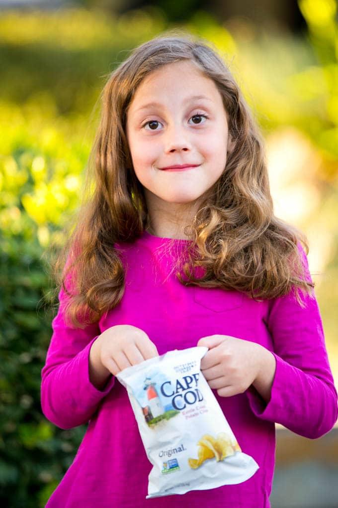 Una niña sosteniendo una bolsa de papas fritas.