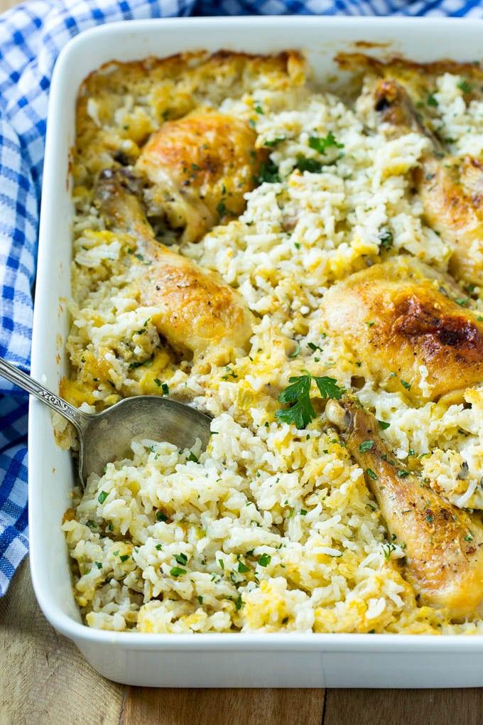 Cazuela de pollo y arroz con trozos de pollo al horno y arroz cremoso en una porción con una cuchara para servir.